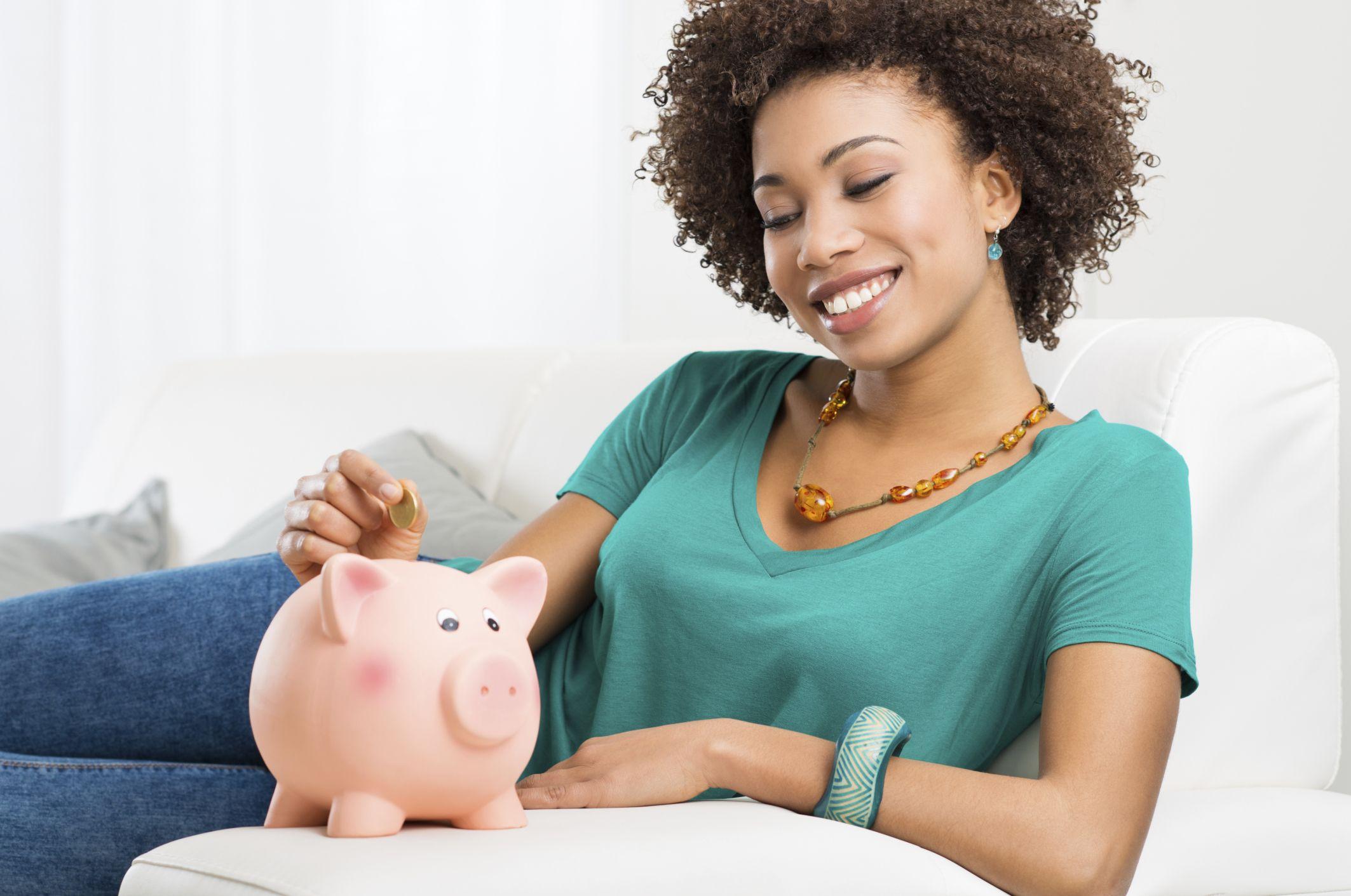 Woman Putting Coin In Piggybank