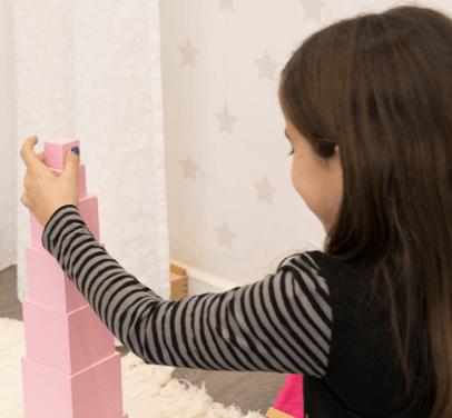Niña construyendo la Torre Rosa, el material Montessori más icónico y representativo del método montessori