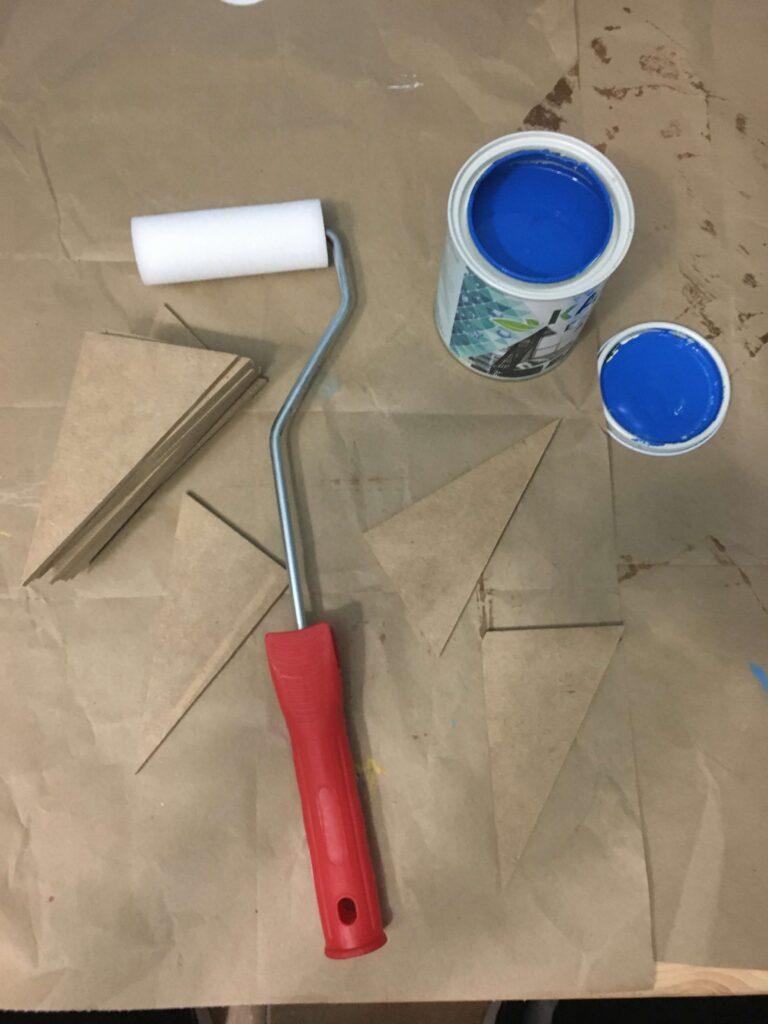 Triángulos azules Montessori DIY listos para ser pintados con el rodillo.