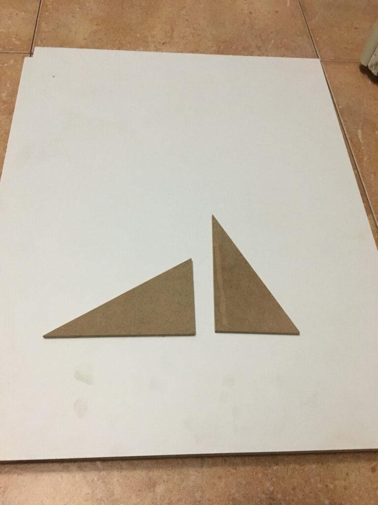 Podemos observar los triángulos azules Montessori de madera en bruto, antes de pintarlos. Recuerda limpiarlos con un trapo húmedo para quitarles el polvo antes de pintar.