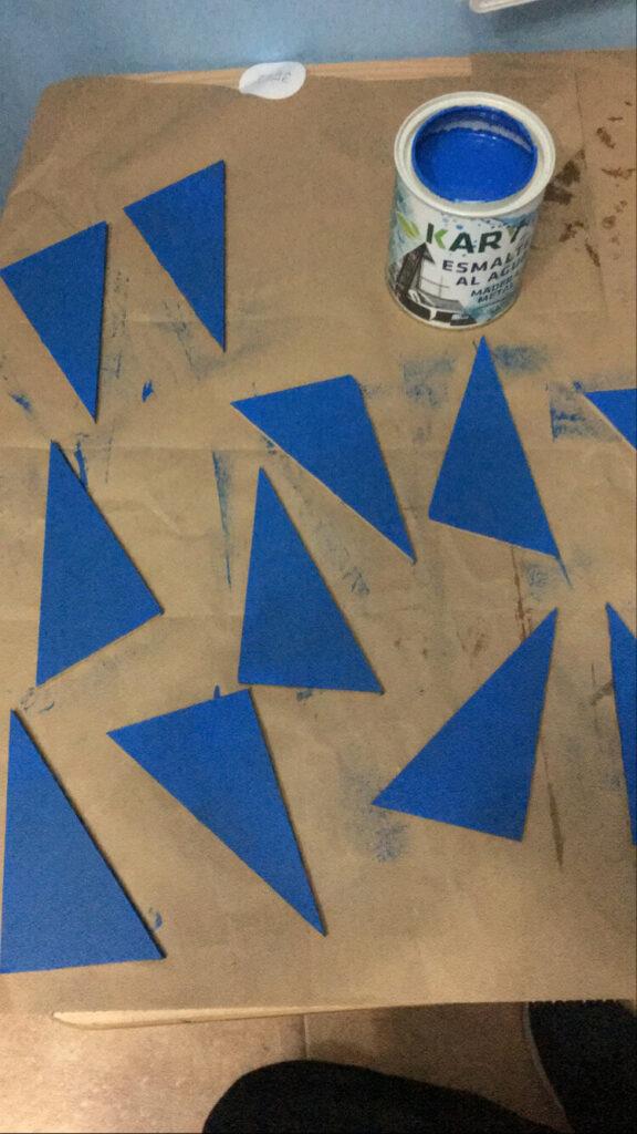 Haz tú mismo los triángulos azules Montessori. En esta imagen, podemos verlos ya pintados y esperando a que se sequen.