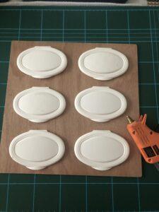 Paso 1: pegar las tapaderas de toallitas húmedas a la tabla con silicona