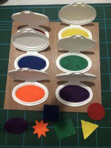 Recortar figuras geométricas de fieltro con los mismos colores del interior de las tapas